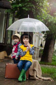 Children with suitcases under umbrella